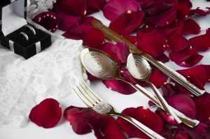 Gravēti galda piederumi uz rožu ziedlapiņām, blakus baltas mežģīnes un divi gredzeni kastītē