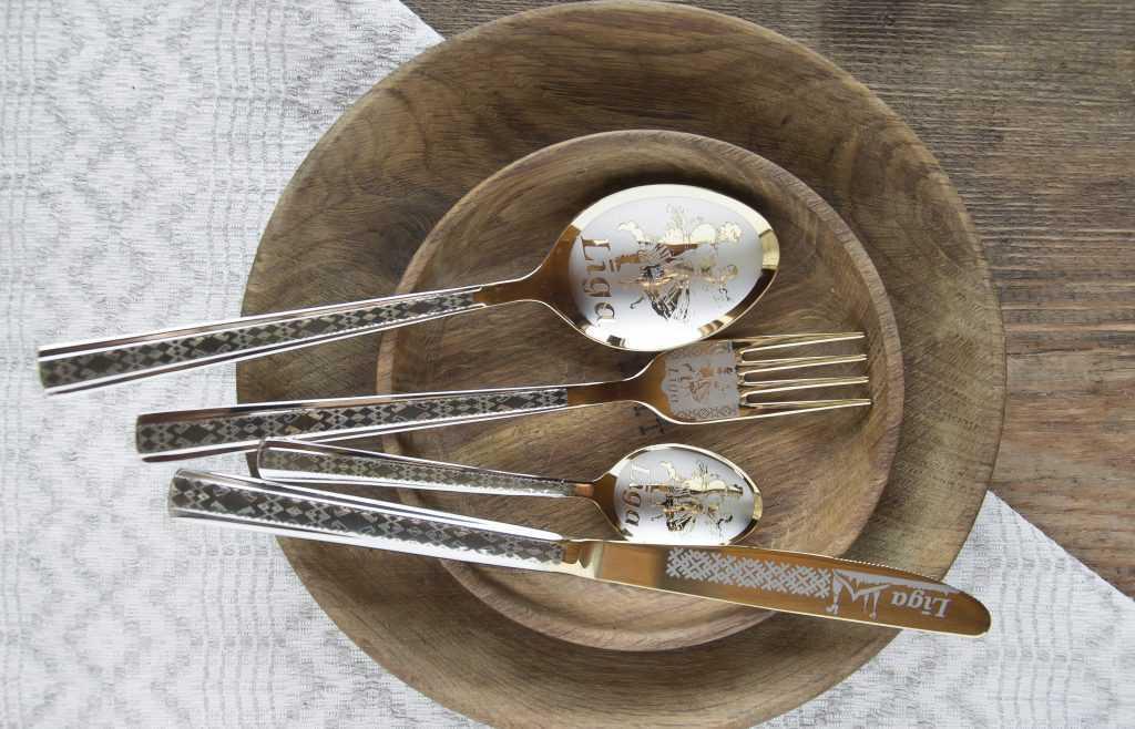 Galda piederumu komplekts ar gravējumiem koka šķīvī, fonā lina galdauts