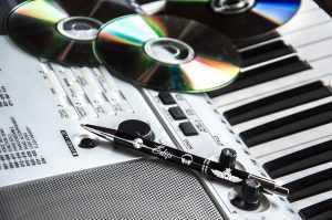 """Melna pildspalva ar gravējumu """"Edijs"""" uz sintizatora, blakus CD"""
