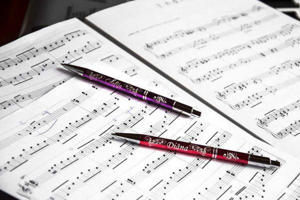 """Divas metāla pildspalvas ar gravējumu """"Diāna"""" uz baltām nošu lapām"""