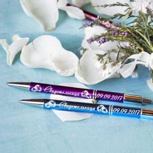 Divas metāla pildspalvas ar gravējumu baltā krāsā, fonā rožu ziedlapiņas