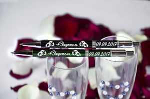 Divas metāla pildspalvas ar gravējumu uz divām šampanieša glāzēm, fonā rožu ziedlapas