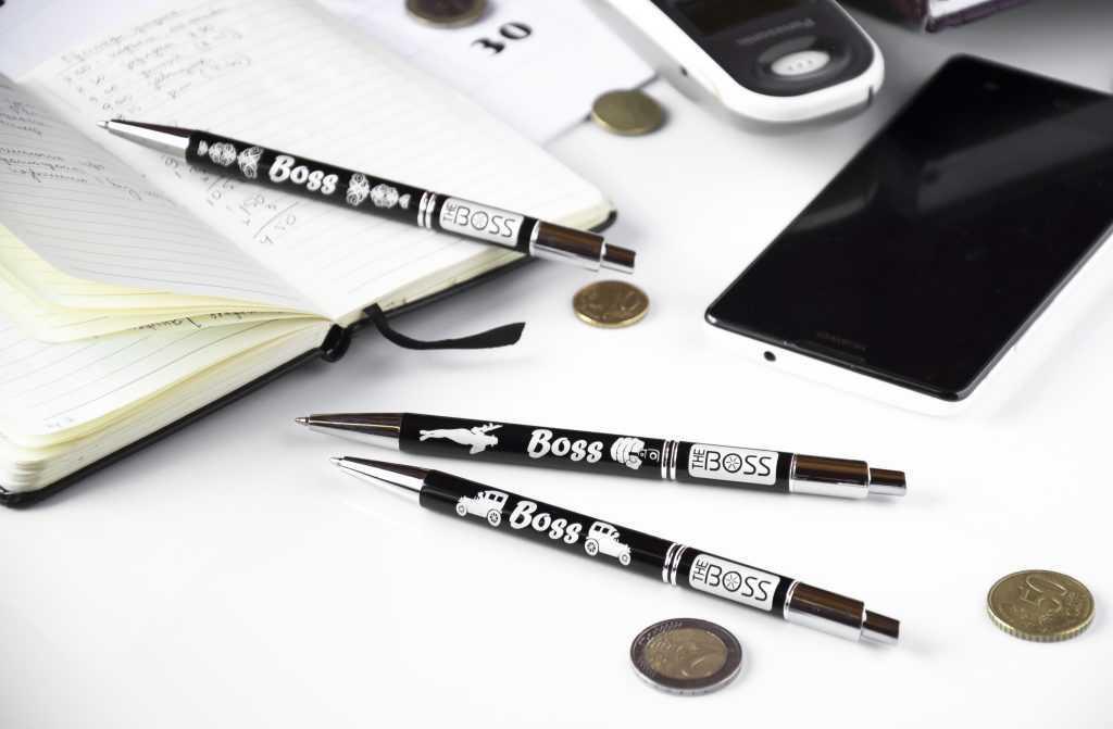 """Trīs melnas pildspalvas ar gravējumu """"Boss"""", eiro monētas, piezīmju bloks un mobilais tālrunis uz baltas virsmas"""