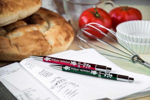 """Divas metāla pildspalvas ar gravējumu """"Mīļajai māmiņai"""" uz piezīmju lapām, blakus maizes klaipi, tomāti, putojamā slotiņa"""