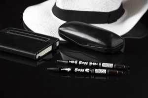 """Divas melnas pildspalvas ar uzrakstu """"Boss"""", melns briļlu maks, piezīmju bloks un balta cepure uz melnas virsmas"""
