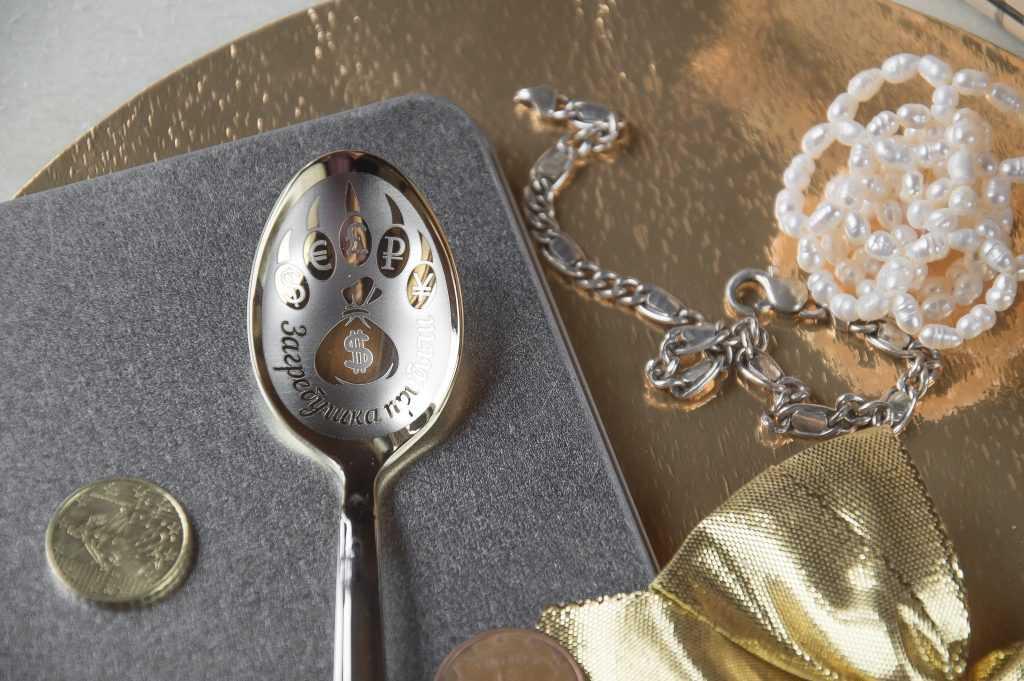 Karote ar gravējumu, blakus metāla ķēdīte, kaklarota un eiro monētas