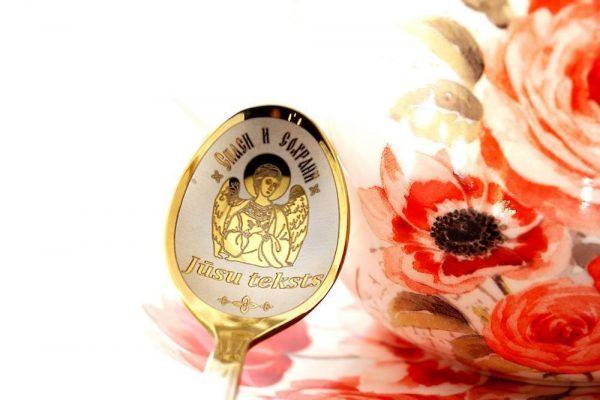 karote zelta krāsā ar iegravētu eņģelīti un fonā krūzi ar magonēm